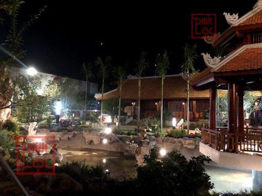ảnh chụp ban đêm nhà gỗ mái ngói sân vườn