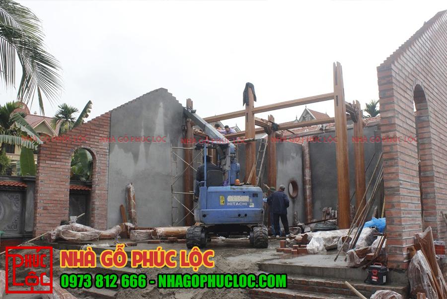 Hình ảnh thợ sử dụng máy móc để lắp dựng cột nhà