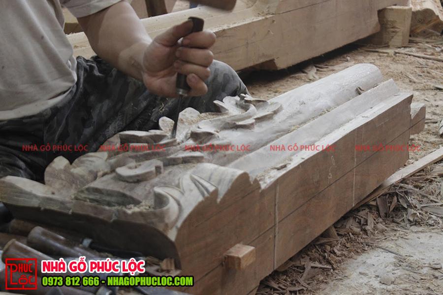 Hình ảnh người thợ đang đục chạm các cấu kiện nhà gỗ cổ truyền