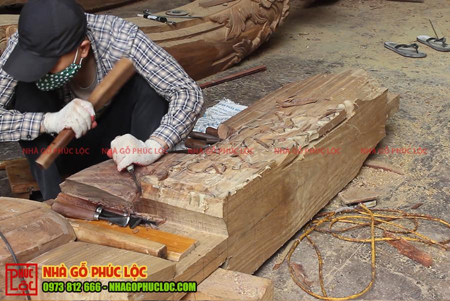 Hình ảnh người thợ chạm đang đục các hoa văn của nhà gỗ