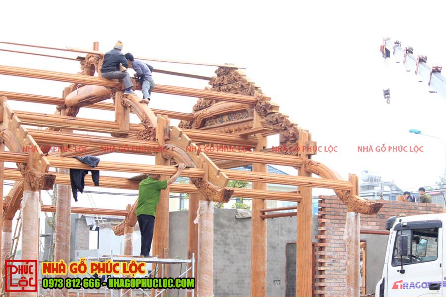 Hình ảnh người thợ đang lắp dựng khung nhà gỗ