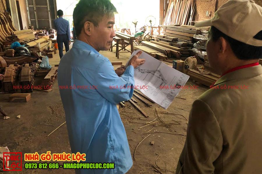 Bác thợ cả chỉ cho gia chủ về bản thiết kế căn nhà gỗ 5 gian