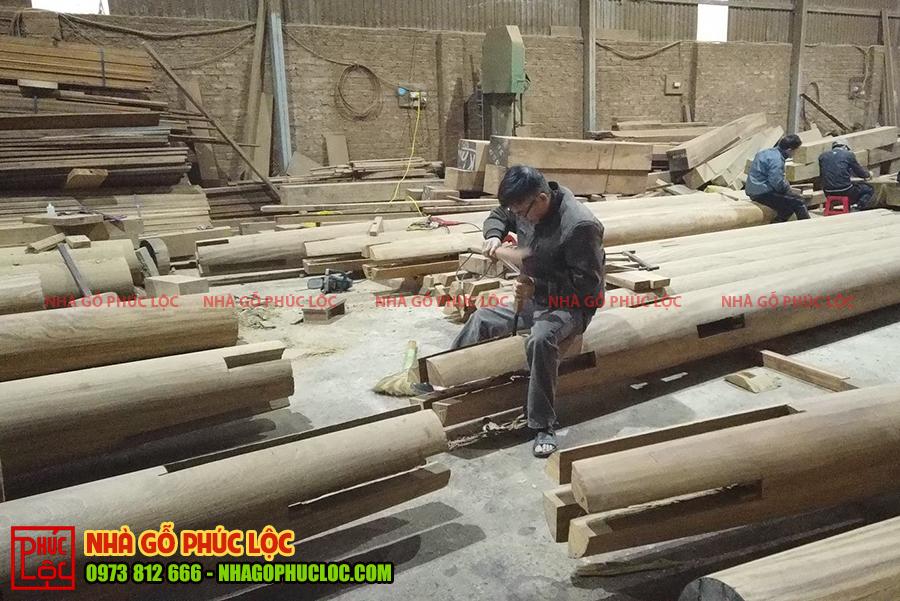 Hình ảnh người thợ đang đục chạm nhà gỗ