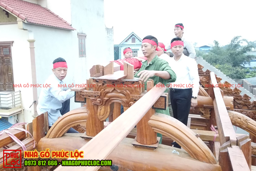 Gia đình và đội ngũ thợ lên phần nóc nhà để gác thượng lương