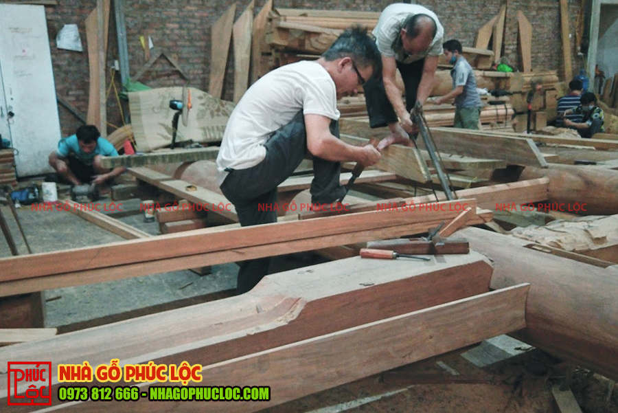 Người thợ sẽ cắt những phần dư thừa của nhà gỗ
