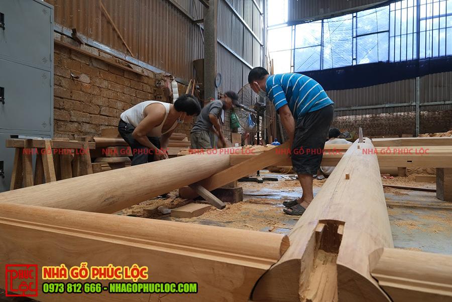 Các cột gỗ lớn cần sự hỗ trợ của cả đội thợ