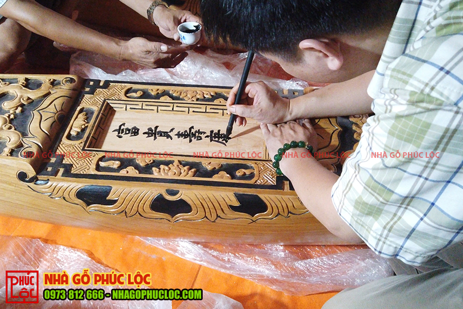 Thầy viết chữ trên câu đầu nhà gỗ